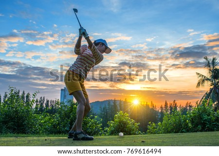 woman golf player in action of top backswing, ready downswing to hit the golf ball away to the fairway ahead, sunset scenery in background