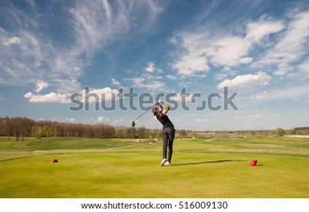 Woman golf player teeing off ball, view from behind.