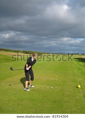 Woman golfer hitting her driver on a beautiful Scottish golf course with moody skies in the background