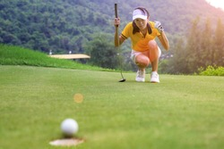 woman golfer in action of exciting of flowing of golf ball run almost to golf hole on the green