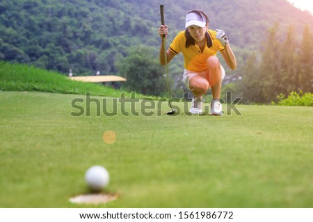 woman golfer in action of exciting of flowing of golf ball run almost to golf hole on the green ストックフォト ©