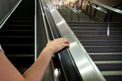 Woman grabbing the escalator hand rail while standing on the escalator, woman going down the stair in the shopping mall by using escalator. Safety awareness in everyday life concept.