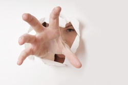 woman grabbing with hand through hole in paper wall