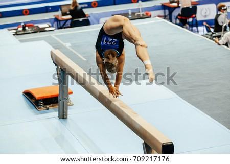 woman gymnast acrobatic skill in balance beam gymnastics