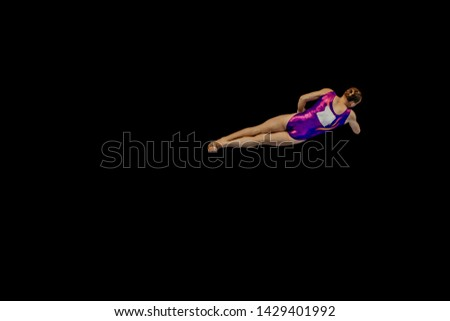 woman gymnast flying in air somersault exercise gymnastics on black background #1429401992
