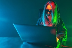 Woman hacker next to a laptop. Girl hacker in the neon light. Hacking. Woman cracker works in the dark. Girl is using a computer. Hacker in sunglasses. Hacking computer networks. Internet attack
