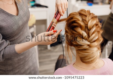 Woman hairdresser making hairstyle to blonde girl in beauty salon. #1095475223