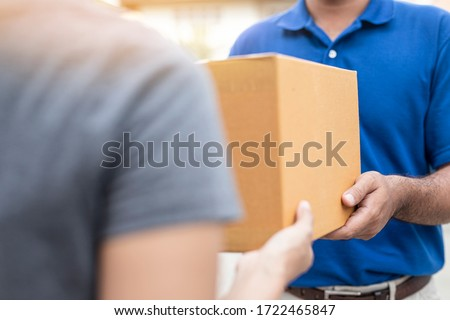 Woman hand accepting a delivery boxes of paper containers from deliveryman,Delivery concept.