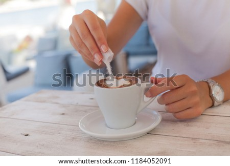 1da87b96f0f6b8 Woman hand adding sugar in the coffee  1184052091 · Isolated woman hand  holding a cup of hot red tea