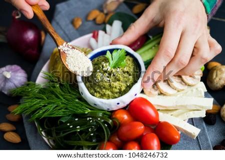 Woman hand adds sesame seeds to healthy veggie buddha bowl with vegetables - cucumbers, tomatoes, radish, mushrooms, seaweed, garlic,  avocado chickpea dip. Closeup view. Raw, vegan, vegetarian food #1048246732