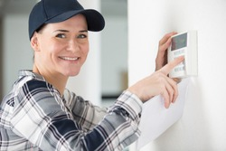 woman hand adjusting a wall mounted thermostat temperature
