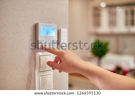 Woman hand adjusting temperature / thermostat