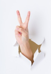 Woman hand breaking through paper wall pointing with the two finger