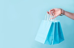 woman hand carrying a bunch of blue shopping bags over blue background with copy space