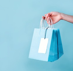 woman hand carrying a bunch of blue shopping bags with a blank tag over blue background with copy space