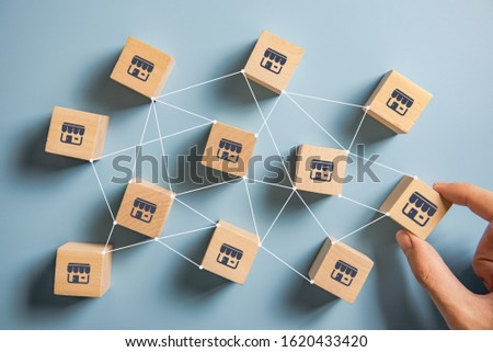 Woman hand choose wood blog with franchise marketing system in global network connection. Franchise business concept. Stockfoto ©