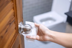 Woman hand cleaning toilet doorknob by wet wipe tissue, protection coronavirus or Corona Virus Disease (Covid-19) at home. Clean surface, Antiseptic, lifestyle, Hygiene and New normal concept