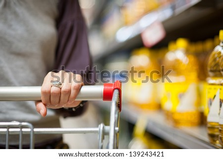 Woman hand close up with shopping cart in a supermarket walking trough the aisle.