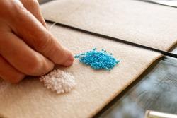 woman hand crafting beaded yewelry