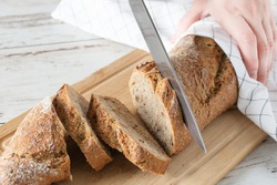 Woman hand cutting loaf of bread on white wooden table. Loaf of wholegrain bread