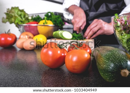 woman hand cutting salad on chopping wood board with sharp knife and cooking vegetables salad in kitchen. - Shutterstock ID 1033404949