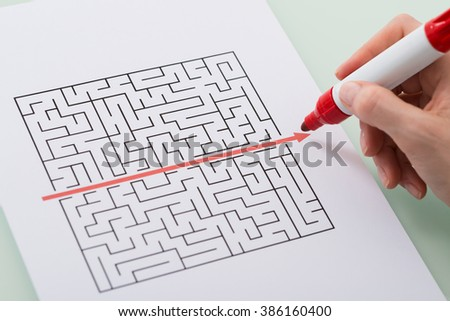 Woman Hand Drawing Straight Red Line Over Maze With Red Marker
