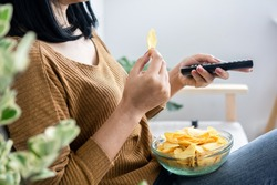 woman hand eating potato chips and holding remote tv watching series sitting on sofa