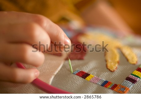 woman hand embroiders with a needle and a thread
