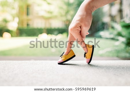 Photo of  woman hand finger walking with shoe concept, Traveler adventure outdoor summer vacations concept, Healthy lifestyle concept. Stay at home quarantine for coronavirus.