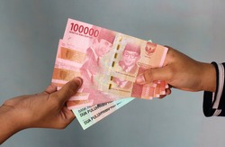 Woman Hand give Indonesian Money Rupiah. Woman hand is holding bunches of Indonesian Rupiah (IDR) Red 100,000 bank notes currency