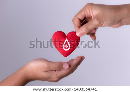 Woman hand gives a red heart to a boy hand for blood donation concept,World blood donor day. Copy space for advertisers.