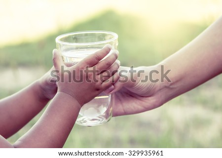 Woman hand giving glass of fresh water to child in the park,vintage color filter #329935961