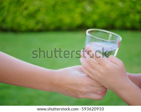 Woman hand giving glass of fresh water to child on the green grass background - Shutterstock ID 593620910
