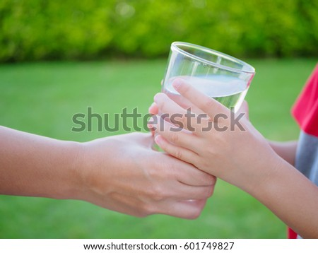 Woman hand giving glass of fresh water to child on the green grass background - Shutterstock ID 601749827