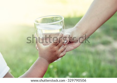 Woman hand giving glass of fresh water to little child girl in the park,soft color filter - Shutterstock ID 329790506