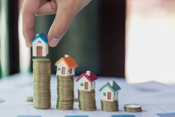 Woman hand hold a  home model put on the stack coin with growing, Savings money for buy house and loan to business investment for real estate concept. Invesment and Risk Management.