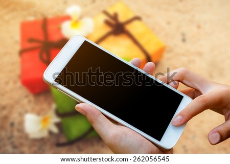 woman hand hold and touch screen smart phone, tablet,cellphone on gift box on sand beach background.