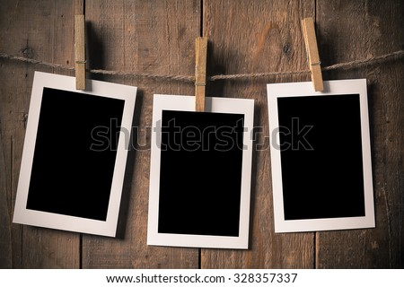 Woman Hand Hold Blank Old Photo Frame Hanging on a Rope By Clothespin