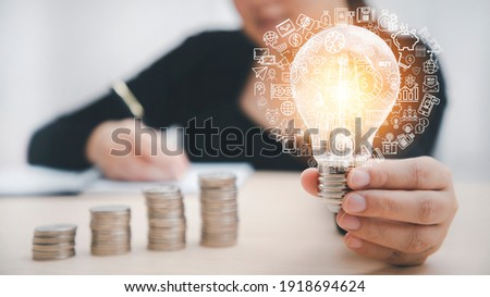 Woman hand hold light bulb with icons work on the desk, Creativity and innovation are keys success. Concept of new idea and innovation with icons and light bulbs, Save the money, Freedom of thought.