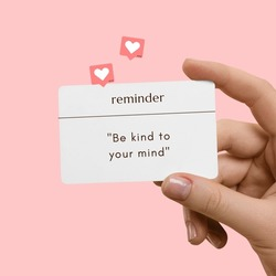 woman hand hold Pink Motivational Quote Reminder. Be Kind To Your Mind