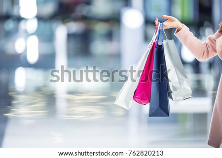 Woman hand holdind shopping bags in shopping mall.