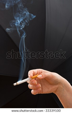 Woman hand holding a cigarette of wisp of smoke
