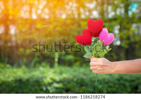 Woman hand holding a flower of heart on sunlight in the public park, for give supporting when people get who lack of desire with love concept. #1186218274