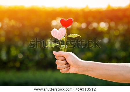 Woman hand holding a flower of heart on sunlight in the public park, for give supporting when people get who lack of desire with love concept. #764318512