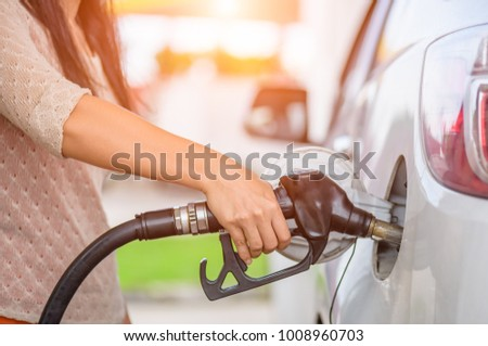 Woman  hand holding a fuel pump at a station.