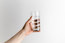 Woman hand holding a glass of water. White background. Covid-19 pandemic concept. Coronavirus