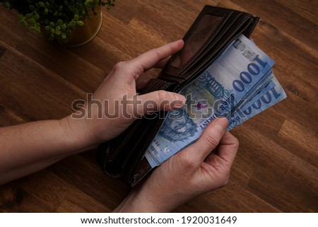 Woman hand holding a leather wallet. Includes Hungarian 1000 forints. Top view of man hand with banknotes on wooden background. Foto d'archivio ©