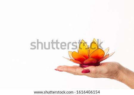 woman hand holding a lotus flower shaped candle holder isolated on white background