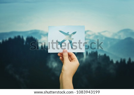 Woman hand holding a paper sheet with plane icon over wild nature background with forest and snowy mountains. Love travel concept.