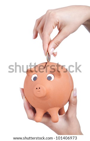 woman hand holding a piggy bank and a coin